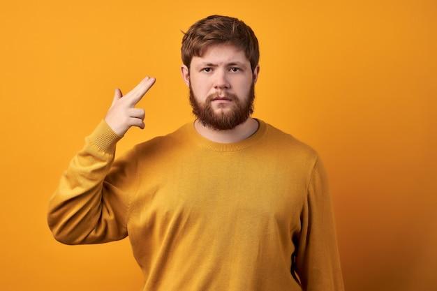 의아해 주저 빨간 머리 남성은 턱을 잡고 우둔한 표정으로 눈썹을 들어 결정을 내릴 수 없으며 무언가에 대해 고민하고 캐주얼 한 흰색 티셔츠를 입고 프리미엄 사진