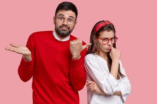 困惑した男は不機嫌そうな表情で気分を害した女性を指差す 無料写真