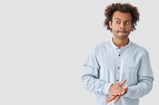 困惑した混血の若い男は唇を噛み、パリッとした髪を持ち、手を一緒に保ち、混乱して脇に見え、ファッショナブルなシャツを着て、白い壁にポーズをとる 無料写真