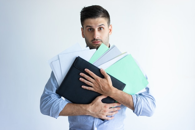 Puzzled office worker holding pile of documents Free Photo