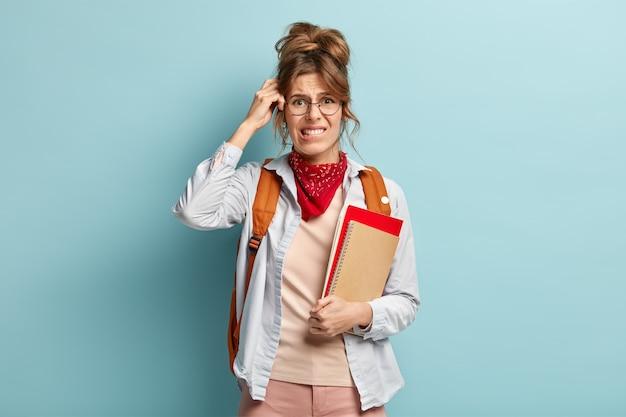 의아해 여학생은 노트와 나선형 일기를 들고, 입술을 물고, 마음에 정보를 기억하며 머리를 긁고, 세련된 두건, 투명한 안경, 배낭을 등에 착용합니다. 개념 공부 무료 사진