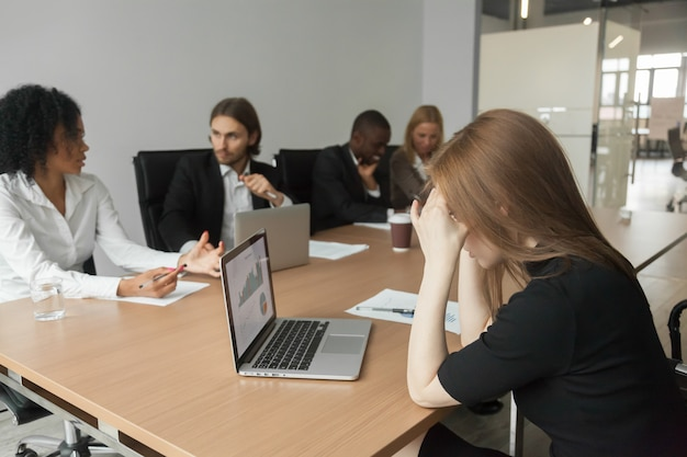 Puzzled serious businesswoman concerned about project statistics at group meeting Free Photo