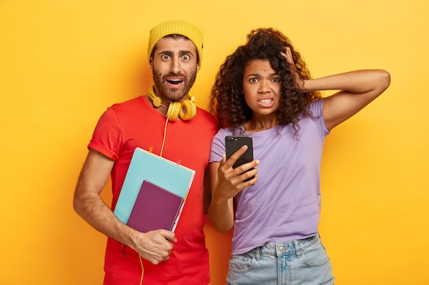 놀란 충격을받은 젊은 여성과 남성이 휴대 전화를 사용하고, 프로젝트 준비 기한이 있고, 함께 공부하고, 캐주얼 한 밝은 티셔츠를 입고, 끔찍한 표정으로 보입니다. 무료 사진