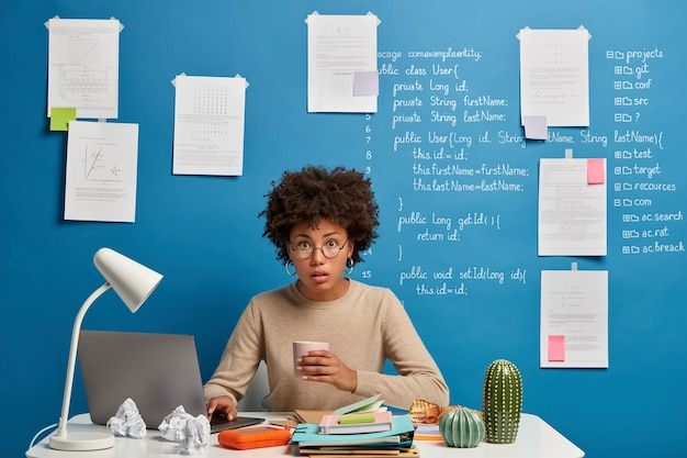 의아해 놀라는 컴퓨터 분석가가 커피를 마시고, 웹 페이지에 게시되고, 둥근 안경을 쓰고, 바탕 화면에 서면 정보가있는 파란색 벽에 포즈를 취합니다. 무료 사진