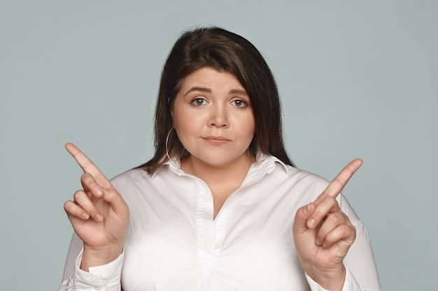 Puzzled young dark haired businesswoman with chubby cheeks and curvy body pointing her index fingers at opposite directions, can't choose between two business concepts, having doubtful look Free Photo