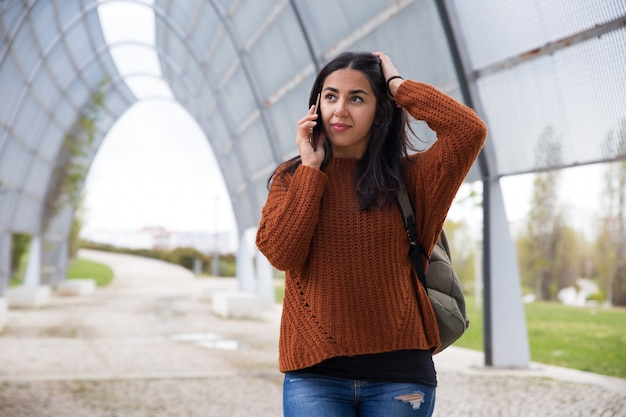 Puzzled young woman talking on cellphone Free Photo