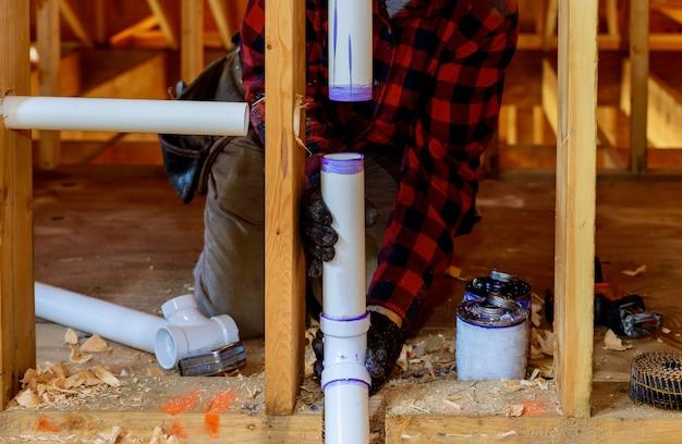 建設家でプライマーと接着剤pvcパイプを設置する配管工 Premium写真