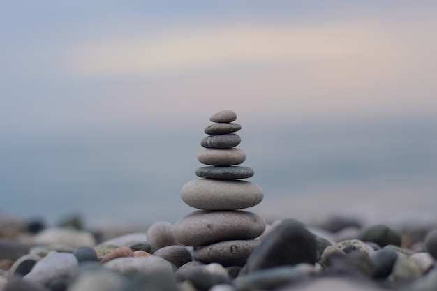 A pyramid of different-sized stones on the shore of the black sea Premium Photo