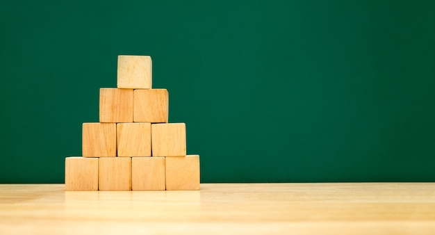 Pyramid shape build from wood cube on wooden table with green blackboard at background Premium Photo