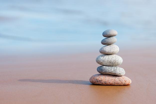 Пирамидные камни балансируют на песке пляжа. объект находится в фокусе, размыто. Premium Фотографии