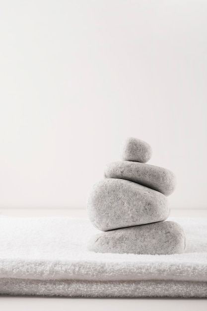 Pyramid of the stones over clean folded towel isolated on white background Free Photo