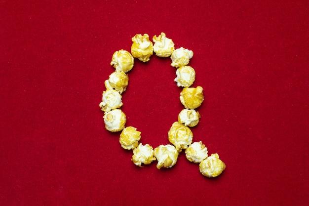 Английский алфавит из кино-попкорна. буква q. красный фон для дизайна Premium Фотографии