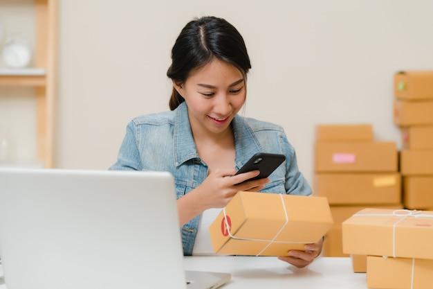 在宅勤務株式スキャンqrコードで製品をチェック中小企業の美しいスマートアジアの若い起業家ビジネス女性の所有者。 無料写真