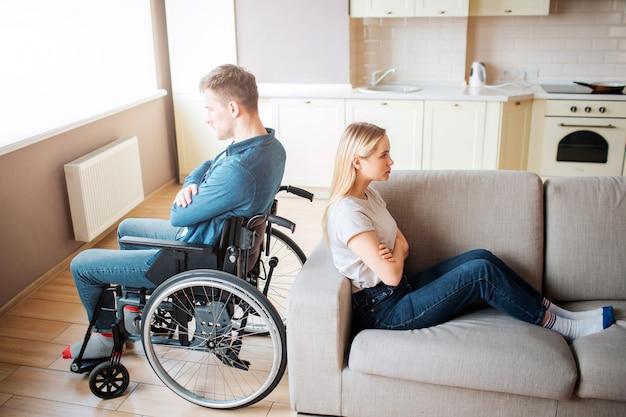 特別なニーズと健康な女性と若い男は部屋で背中合わせに座っています。口論とqu。障害および包括性のある労働者。動揺して不幸なカップル。 Premium写真