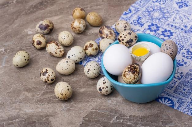 파란색 컵에 메추라기 및 닭고기 달걀 무료 사진