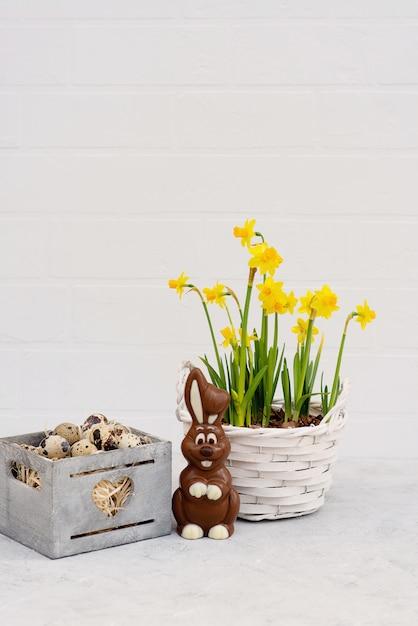 新鮮な水仙の花とチョコレートのイースターのウサギと木製のバスケットのウズラの鳥の卵。 Premium写真