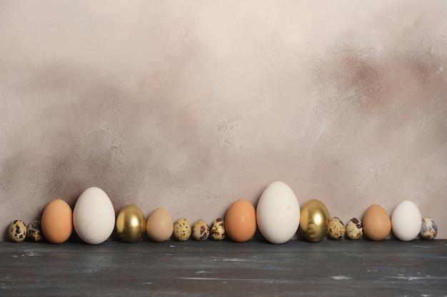 さまざまなサイズと色のウズラ、鶏、ガチョウ、ホロホロ鳥の卵が古い壁に並んでいます。 Premium写真