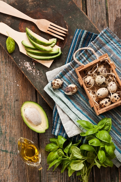 Quail eggs, avocado and fresh green ingredients for spring salad. dietary healthy food Premium Photo