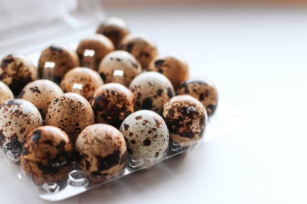 Quail eggs in a box on a white background copy space Premium Photo