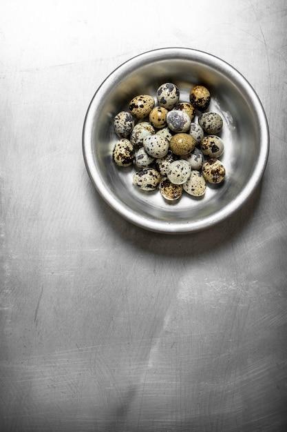 金属製のテーブルの上の金属製のボウルにウズラの卵 Premium写真