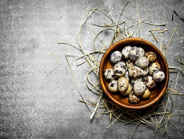 石のテーブルの干し草のボウルにウズラの卵。 Premium写真
