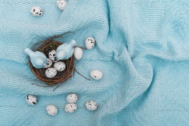 Quail eggs in nest on blue cloth Free Photo