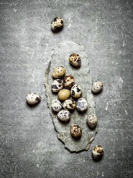 石のテーブルの上のウズラの卵。 Premium写真
