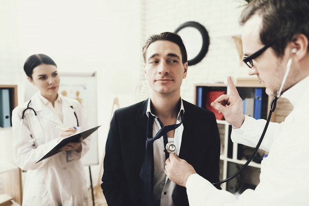 Qualified cardiologist listening to patient's heartbeat. Premium Photo