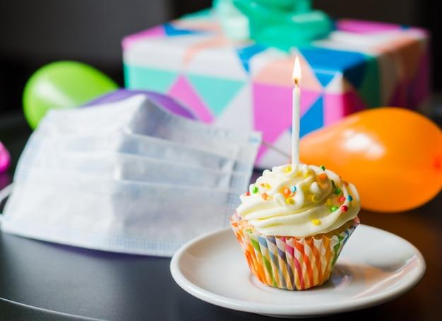 격리 검역 생일. 생일 컵 케 익, 얼굴 마스크, 선물 및 휴가 액세서리. 프리미엄 사진