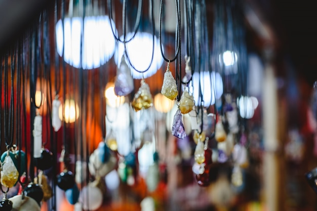 Quartz and other precious stones hung on necklaces in a mineral and beauty shop. Premium Photo