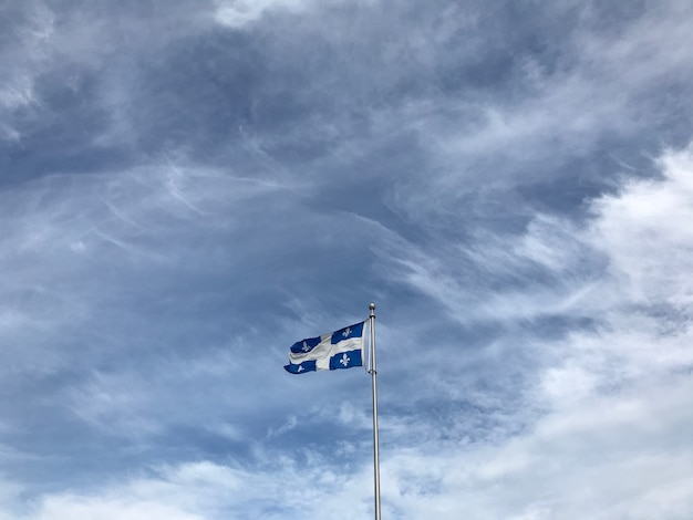 Bandiera del quebec sotto le bellissime nuvole nel cielo Foto Gratuite