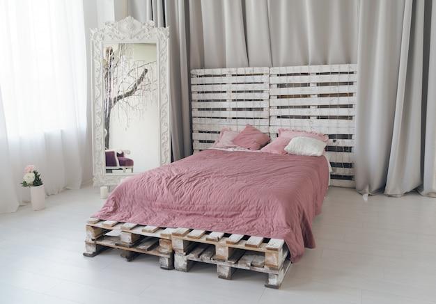 明るい寝室に木製パレットと大きな木製ミラーで作られたクイーンサイズのベッド Premium写真