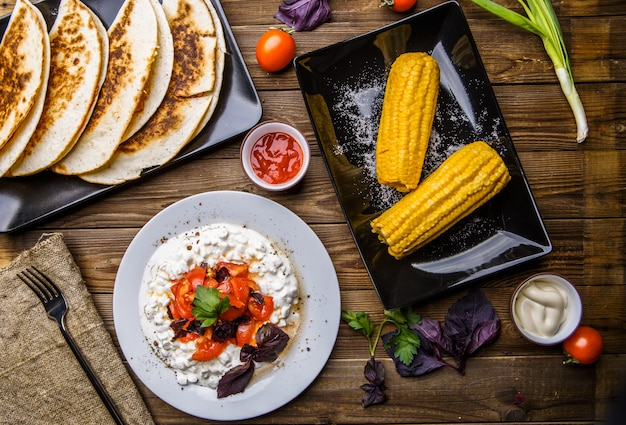 Quesadilla, salad with cottage cheese and tomatoes, two corn on wood table. Premium Photo