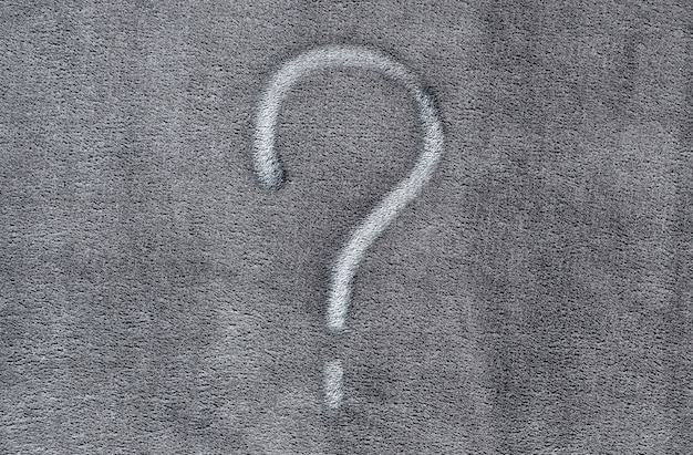 Question mark on gray fabric texture background Premium Photo