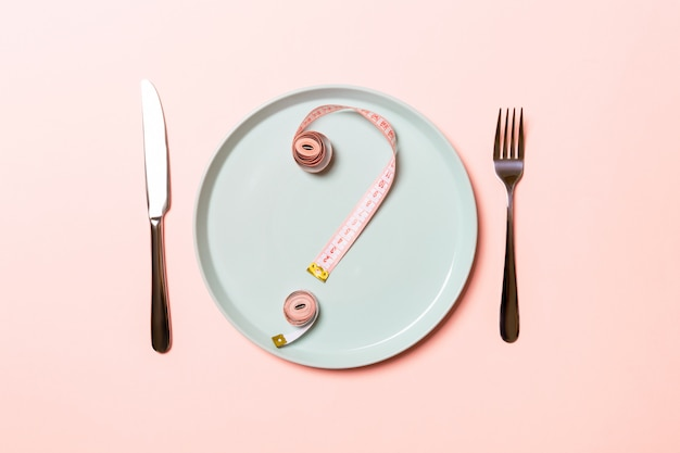 Question mark made of measuring tape on round plate on pink Premium Photo