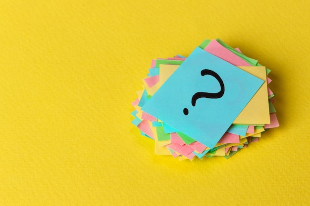Question mark paper heap on yellow background Premium Photo