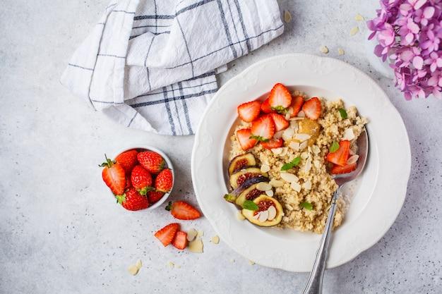 Quinoa breakfast porridge with strawberries and figs in white plate. healthy breakfast. Premium Photo