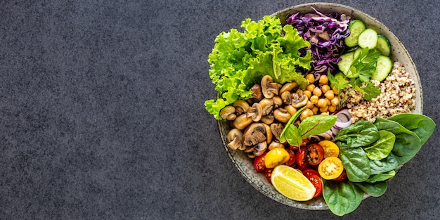 Quinoa, mushrooms, lettuce, red cabbage, spinach, cucumbers, tomatoes, a bowl of buddha on dark, top view. Free Photo