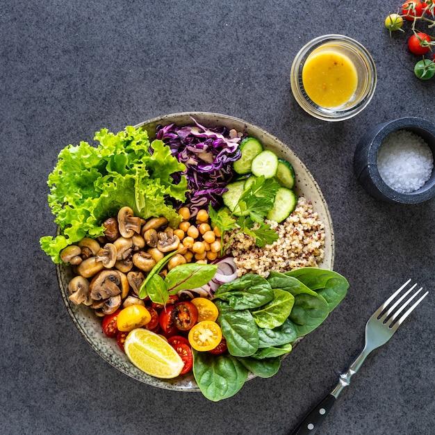 Quinoa, funghi, lattuga, cavolo rosso, spinaci, cetrioli, pomodori in una ciotola di buddha Foto Gratuite