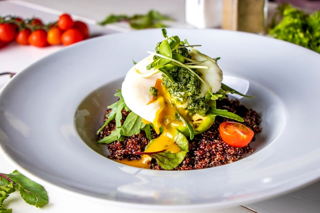 Quinoa with avocado, poached egg and microgreen in a white plate Premium Photo