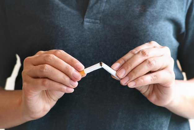 Quit smoking, no tobacco day, woman hands breaking the cigarette Premium Photo