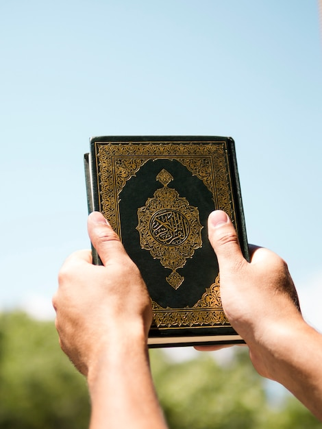 Quran being held up in the sky Free Photo