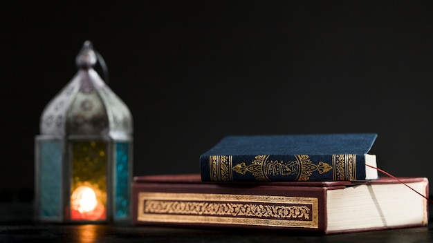 Quran book on table with candle beside Free Photo