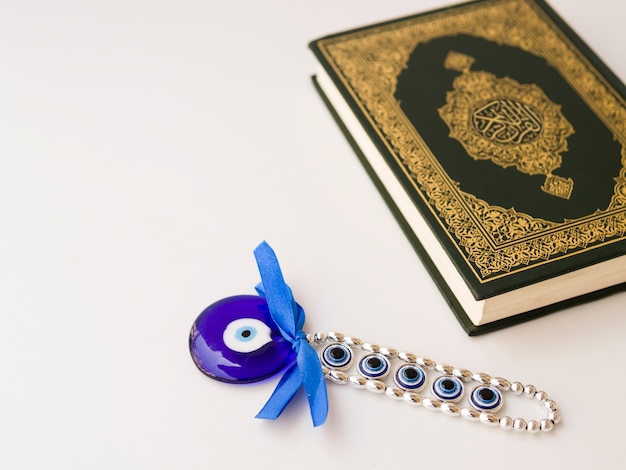 Quran on table with eye of allah amulet Free Photo