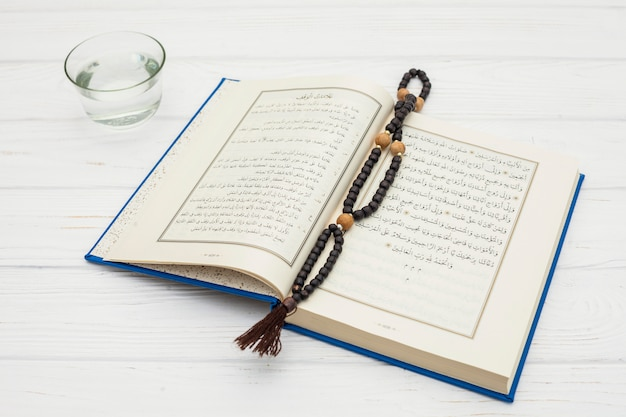 Quran with rosary beads and water in bowl Free Photo