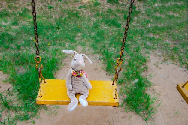 Rabbit doll  on a swing. Premium Photo