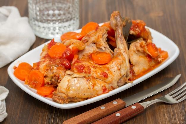 Тушеное мясо кролика с морковью на белом блюде Premium Фотографии