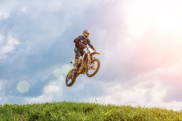 Racer on a motorcycle in flight, jumps and takes off on a springboard against the sky. Premium Photo