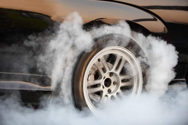 Racing car burns rubber off its tires in preparation for the race Premium Photo
