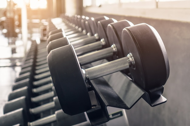 Rack of many sizes of dumbbell in gym sport club. Premium Photo